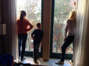Backs of three people silhouetted against a large window