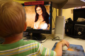baby at a computer looking at a scantily clad woman