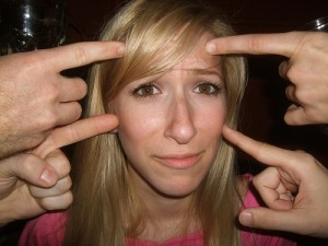 4 pointer fingers in a young woman's distraught face