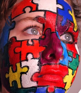 woman's face with red, yellow, white, green and blue puzzle pieces painted on, with a missing piece around her right eye