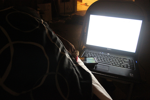 a dark room with a laptop screen glowing in a bed