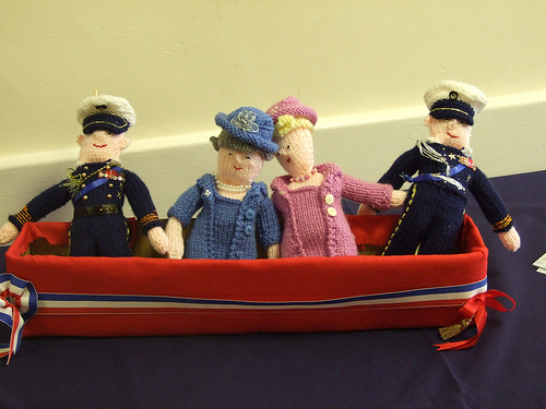 a small balcony with tiny knitted versions of the queen et al
