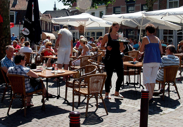 wait staff and customers on a sunny terrace in Europe