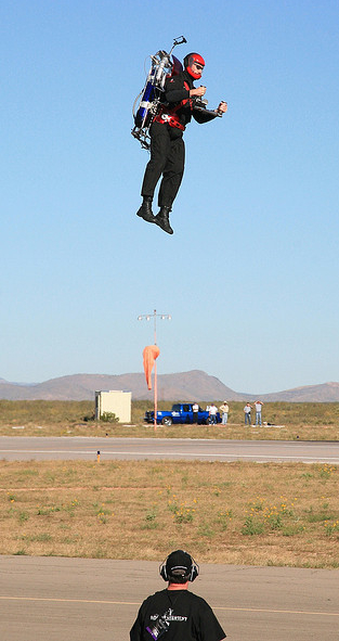 picture of lone man in airfield hovering about 20 feet above the ground using a two cylinder jet back pack