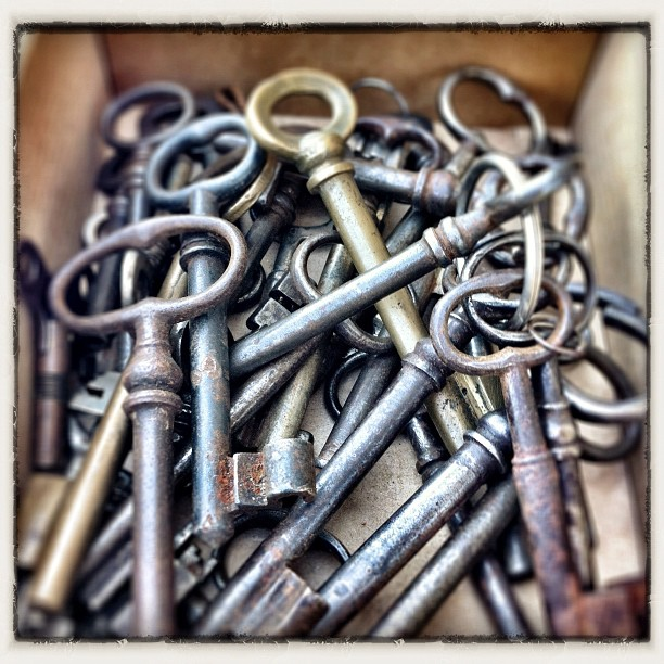 a bunch of old timey skeleton keys in a box