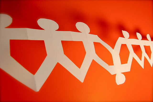 orange background, white paper cut out men with one upside-down