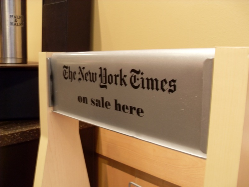 "picture of a sign that says ""NY TIMES ON SALE HERE"""