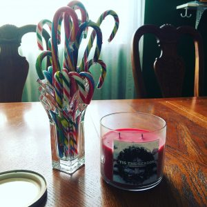 a candy cane pile and a christmas candle