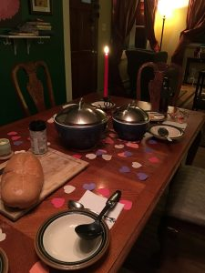 a set table with one candle and paper hearts spread across it