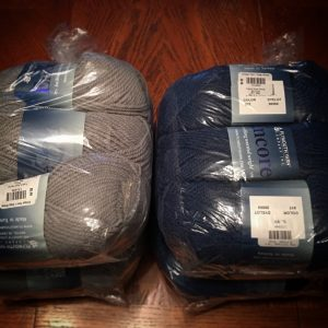 a picture of skeins of yarn in gray and blue, wrapped in plastic