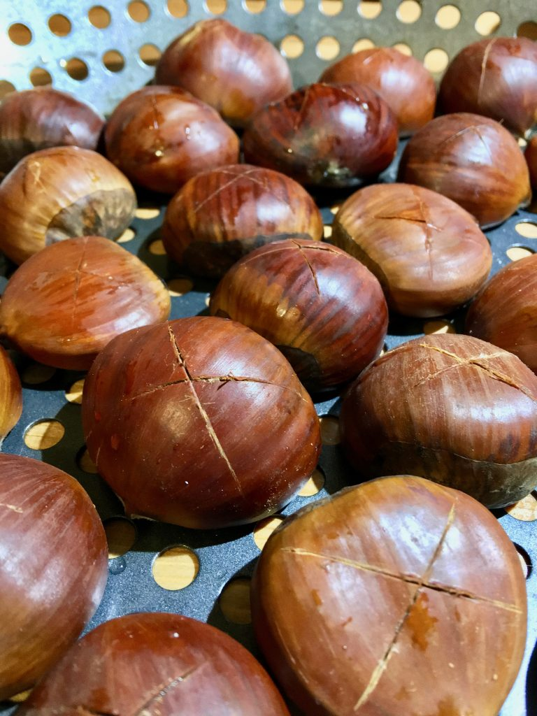 "2-inch chestnuts, scored with an ""x"" on their rounded shell surfaces"