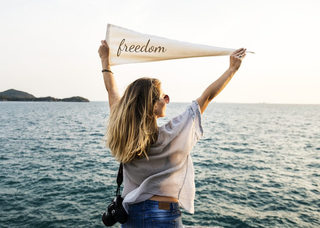 "young white woman holding a pennant flag that says ""freedom"""
