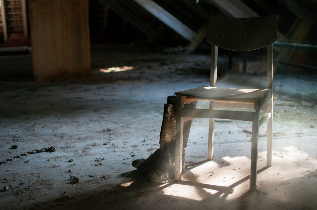 empty wooden chair against a background of abandoned room