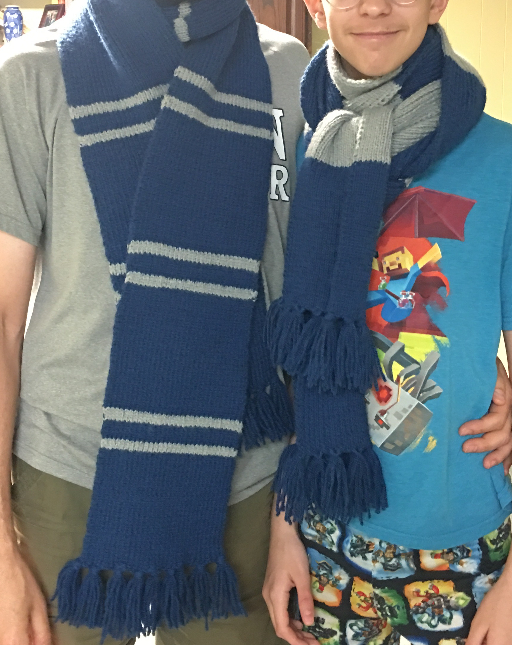 picture of two human torsos modeling two different scarves made in the style of the Harry Potter movies