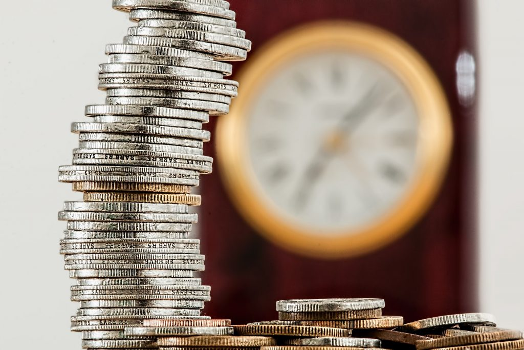 a tall, single pile of coins set against a blurred clock in the background