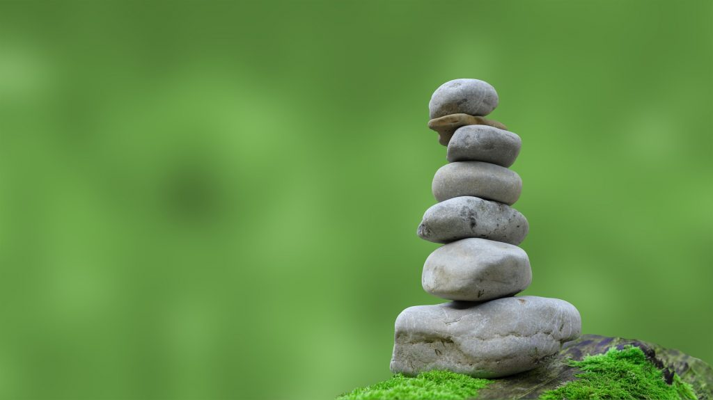 a pile of balanced smooth stones arranged in bigger to smaller sizes vertically, from the ground up. Set against a blurred nature (green) background