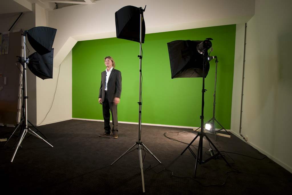 White male, 30s, standing in front of lights and a camera with a green screen behind him