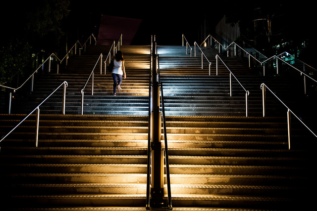 a picture looking up a big flight of metal stairs at night, empty but for one woman walking up them