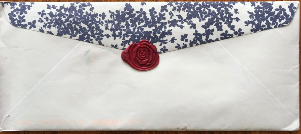 back of a white envelope with a blue floral patterned flap. Flap is sealed with a red wax seal in the shape of an open rose