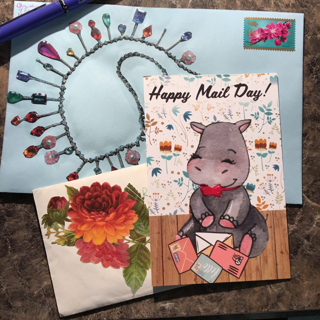 "two letters and a postcard, with no addresses showing. Envelopes have decoupaged decorations like a jeweled necklace and some flowers. The post card is a cartoon drawing of a happy elephant sitting on a wood floor in front of floral wallpaper. She has 4 letters in front of her. The title is ""Happy Mail Day!"""