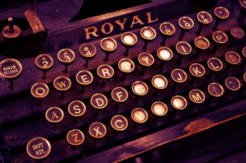 a close up photo of an old ROYAL typewriter with round keys. sepia toned.