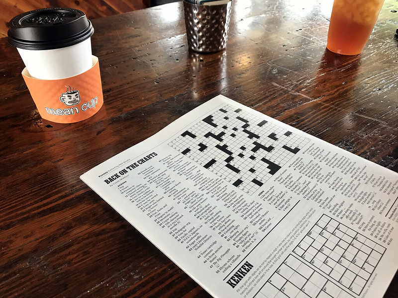 a newspaper opened to the crossword on a wood table in a cafe
