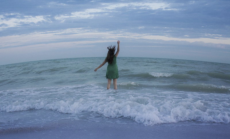 woman in an above-knee green dress facing the ocean. Her back is to us, her right arm is raised in a wave, and she is standing in the surf up to her knees