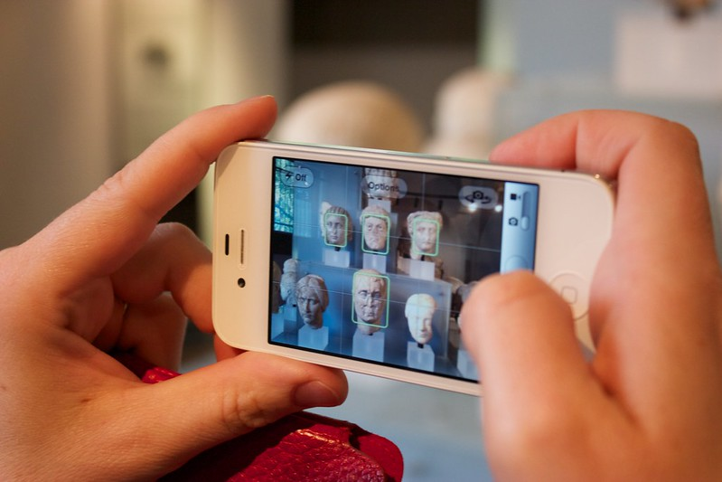 a pair of caucasian hands holding a white iphone in horizontal orientation. It is in photo mode and is taking a picture of roman bust sculptures. The green face-tagging boxes are around the faces of the sculptures