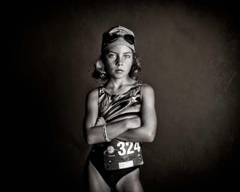 black and white photo of a preteen female athlete in a swim suit, swim cap, goggles and a race number pinned to her suit.