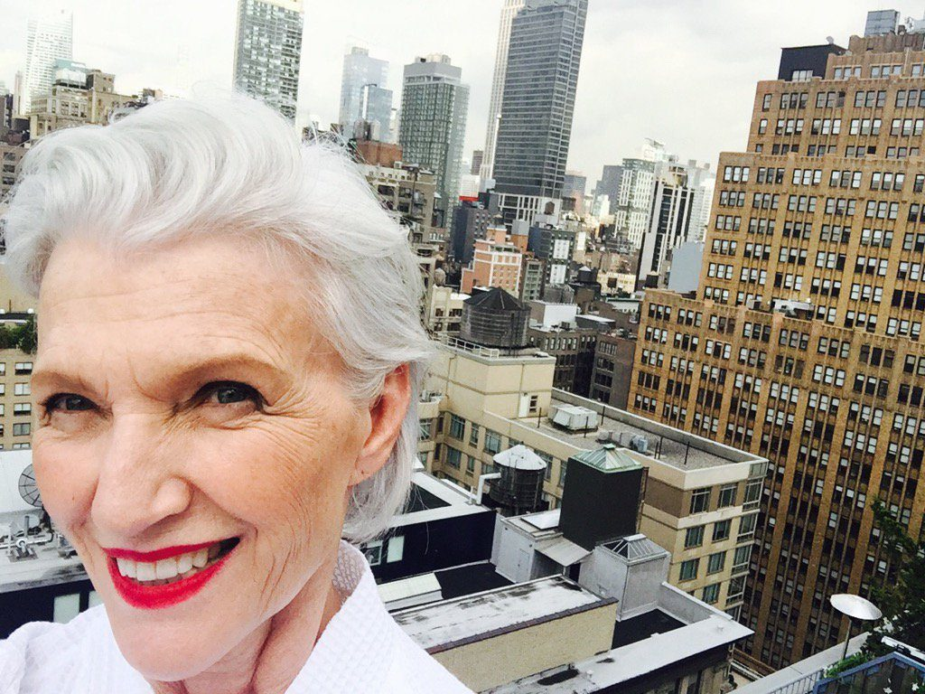 Picture of 70-something white female model with white short hair on the top of a building in a city with the skyline behind her.