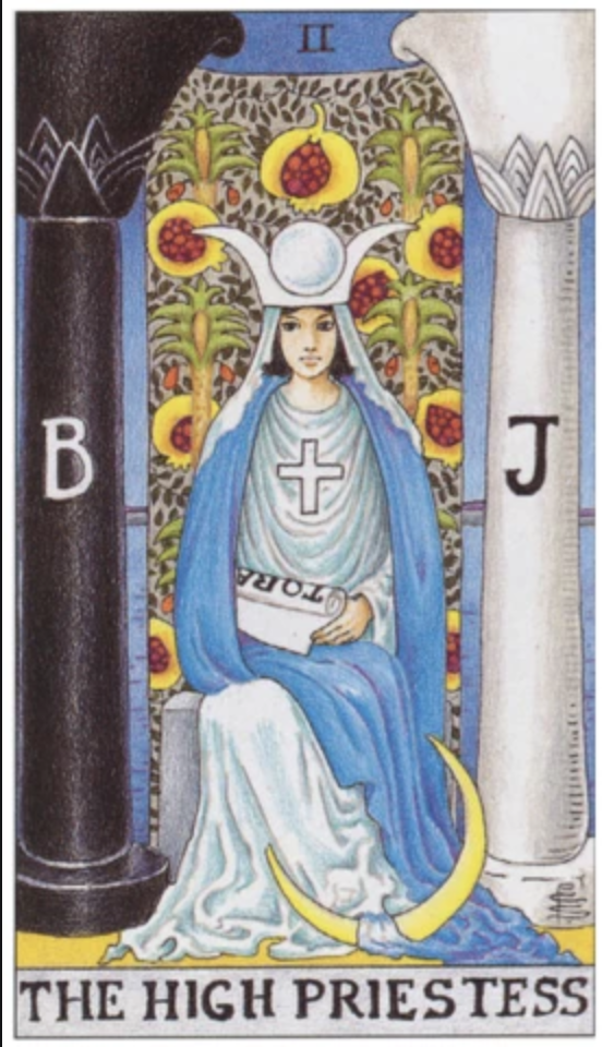 A white woman with dark hair sits on a religious throne surrounded by draperies and many religious symbols of every major world religion. She holds a scroll. There is a black column to her right emblazoned with a B and a white column to her left emblazoned with a J.
