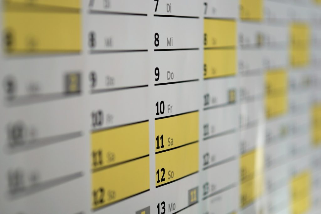 a close up of a very dense wall calendar month view with weekends highlighted in yellow. Black print. Abbreviated days of the week are in another language, maybe Portuguese