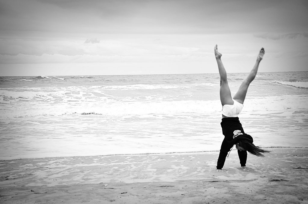 black and white photo of a person on the beach doing a handstand