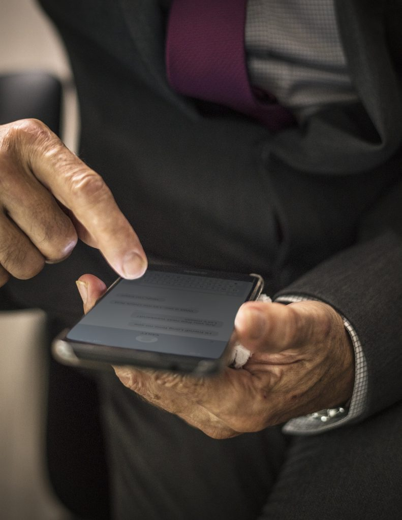 torso of a man in a business suit, close up on his hands holding a phone in an action that looks like scrolling