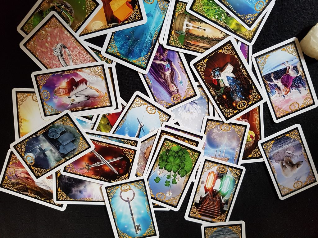 a scattered deck of colorful tarot cards with faces up against a black background