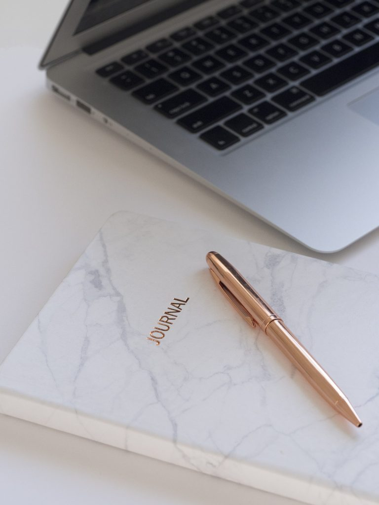 A mostly white page with a marbled cover journal, a gold pen atop it, and a corner of a laptop above them