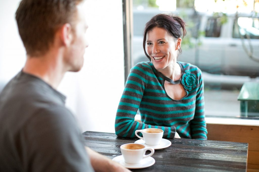 white woman in her late 20s with dark hair and green and black striped shirt sitting in a coffee shop front of a big window. She has a latte in a white ceramic mug and is sitting across from a white male, same age, in a gray t-shirt. He also has a latte in a white ceramic mug. We do not see his face and he is blurred a bit.