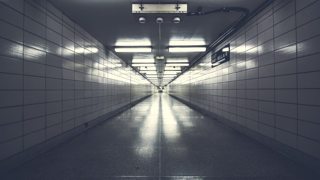 a white tiled hallway, very long, disappearing into one point perspective. Bleak with fluorescent lighting. Empty.